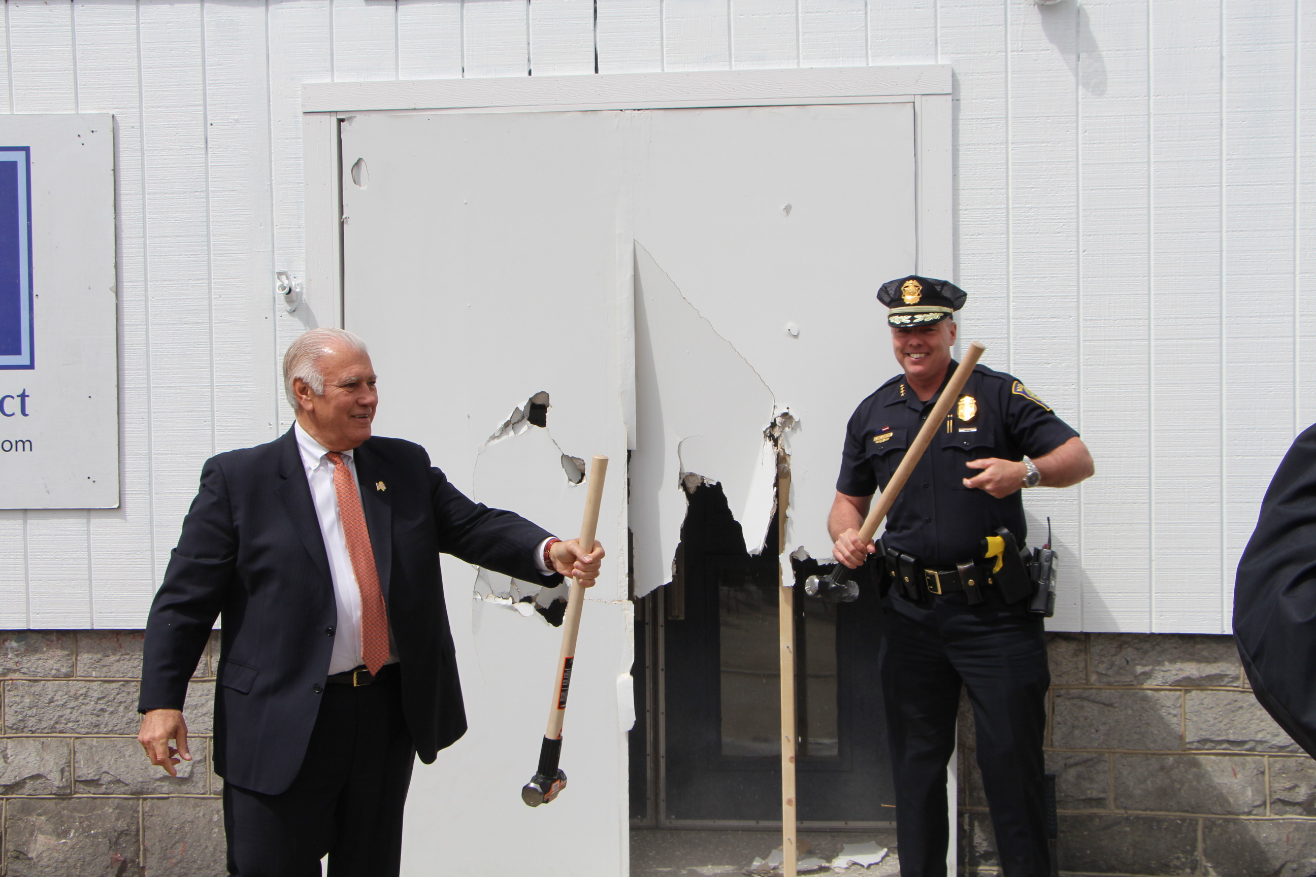 Photo 3: Manchester Mayor Ted Gatsas and Manchester Police Chief Nick Willard break through the entrance of MPAL's Michael Briggs Community Center to celebrate the kickoff of Building on Hope's Build Week 2016.
